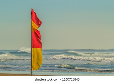 "A red and yellow ""Swim between the flags"" swim safety flag on an Australian beach."