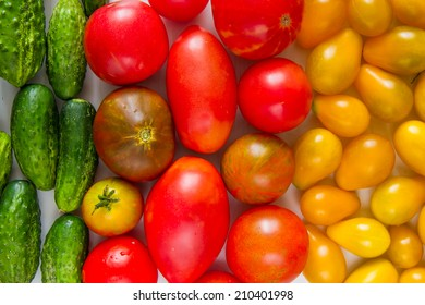 Red and yellow tomatoes and cucumbers on white background