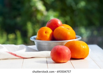 Red and yellow tomatoes in an old aluminum bowl on a wooden board outdoors. Tomatoes background.