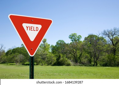 Red Yield Sign With Blue Sky, Green Trees and Grass