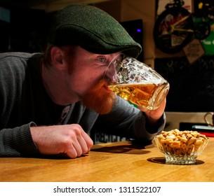 Redbeard Irish guy drinks beer on in the bar. He is maybe drunk but he is very happy!