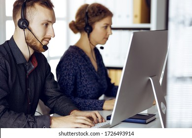 Red-bearded businessman talking by headset near his female colleague while sitting in modern sunny office. Diverse people group in call center