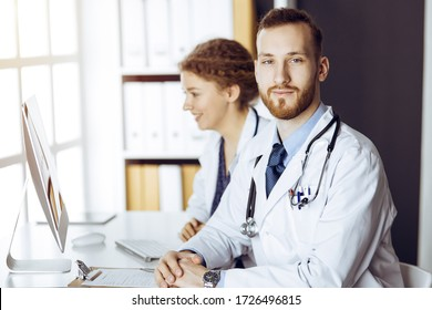 Red-bearded doctor with female colleague discussing current disease therapy while sitting at working place in sunny clinic. Team work in medicine