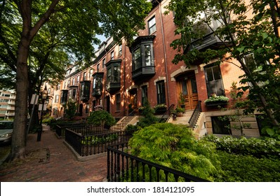 Redbrick apartment building with green bay windows in Victorian style, a little garden in front of it, and the narrow redbrick sidewalk in the shadow of large trees on the left in downtown of Boston