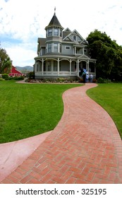 A red-brick walkway leads to a Victorian farm house in Southern California.