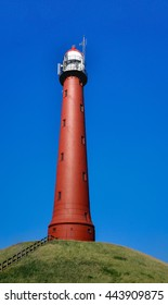 The red-brown painted round cast iron High Lighthouse near the Dutch seaport of IJmuiden is built on a hill in 1878 and 35 meters high. It is a sunny day in the summer season.