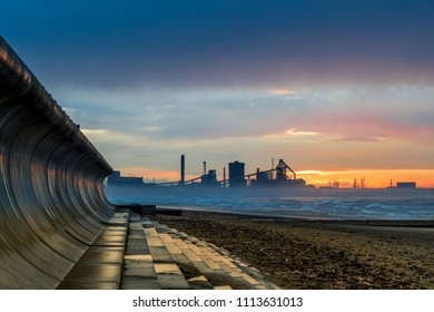 Redcar beach at sunset. North east coast of England. Industrial background. Old abandoned steel works.