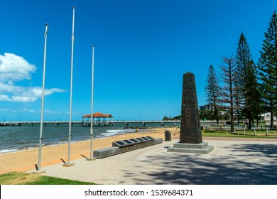 Redcliffe, Queensland, Australia, 10/21/2019: the main obelisk and plaques featured in the ANZAC memorial at the Redcliffe waterfront with the Jetty and Moreton Bay in the background