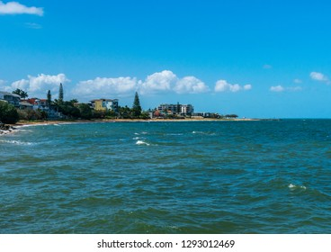 Redcliffe, Queensland, Australia - 1/13/2019: the northern Redcliffe waterfront and beaches viewed from the Redcliffe Jetty with a calm Moreton Bay and scattered clouds in the distance