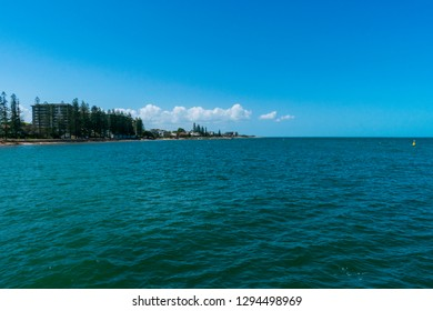Redcliffe, Queensland, Australia - 1/13/2019: The northern end of the Redcliffe waterfront with a calm moreton bay viewed from the Redcliffe Jetty illuminated by the late afternoon sunlight