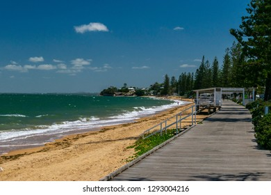 Redcliffe, Queensland, Australia - 1/13/2019: The southern end of the Margate waterfront and wooden slat walkway with the Woody Point shoreline and a calm Moreton Bay illuminated by the afternoon sun