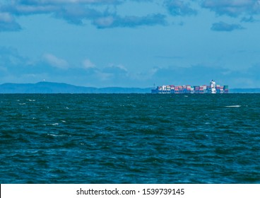 Redcliffe, Queensland, Australia, 22/10/2019: a calm Moreton Bay with a cargo ship sailing along the horizon with  sparse rain clouds and a light summer sky in the background