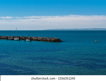 Redcliffe, Queensland, Australia, 31/3/2019: the southern end of the Redcliffe Jetty tidal wall with three small sail boats, a calm Moreton bay and the northern end of Moreton Island in the background