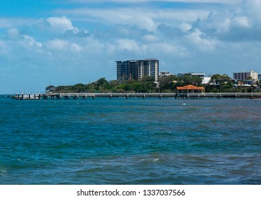 Redcliffe, Queensland, Australia, 3/6/2019: a distance side profile of the Redcliffe pier and shelter viewed from the northern foot path with calm Moreton bay and blue sky with storm clouds