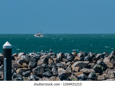 Redcliffe, Queensland, Australia, 3/6/2019: A fishing trawler sails northwards over a calm Moreton Bay with a clear blue sky in the background and the Redcliffe Jetty's tidal wall in the foreground
