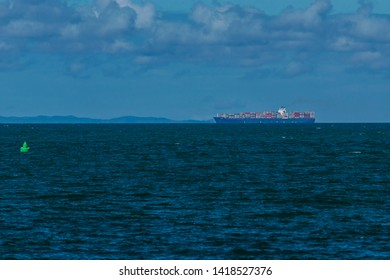 Redcliffe, Queensland, Australia, 5/24/2018: a calm Moreton Bay with a cargo ship sailing along the horizon with Moreton Island and sparse rain clouds in the background
