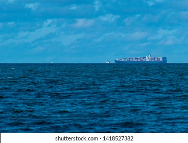 Redcliffe, Queensland, Australia, 5/24/2018: a calm Moreton Bay with a cargo ship sailing along the horizon with  sparse rain clouds and a light autumn sky in the background