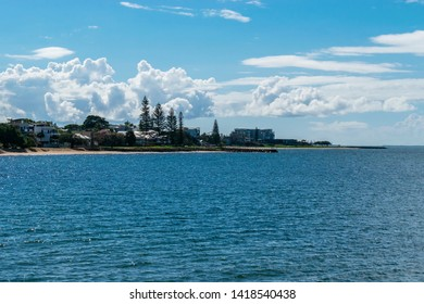 Redcliffe, Queensland, Australia, 5/24/2018: a calm moreton bay with Queen's Beach and the southern Scarborough waterfront on the horizon with sparse clouds and a light autumn sky in the background