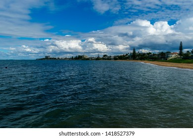 Redcliffe, Queensland, Australia, 5/24/2018: the northern end of the Redcliffe beach fronts with a calm moreton bay and jetty with rain clouds passing beneath the dark blue autumn sky