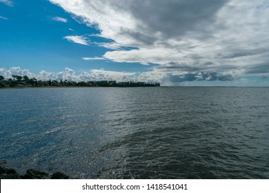 Redcliffe, Queensland, Australia, 5/24/2018: a thick bank of rain clouds pass over a calm moreton bay with Queen's Beach and the southern Scarborough waterfront in the background