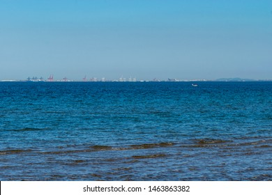 Redcliffe, Queensland, Australia - 7/19/2019: a calm moreton bay with the Brisbane dockyards city skyline and container ships on the horizon viewed from the Woody Point jetty