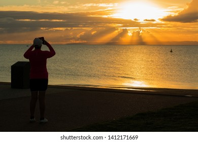 Redcliffe, Queensland/ Australia- May, 25, 2019:A woman stopped her morning walk to photograph the beautiful sunrise with her mobile phone at Redcliffe War Memorial Park in Redcliff, Australia.
