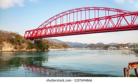 A red-colored bridge called 'Mukaishimao Bridge', which connects Mukoujima Island and Iwashi Island, along the Shimanami Kaido in the Shikoku Region in Japan.