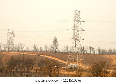 Redding, CA - August 06, 2018: PG and E crew working on the power lines in fire decimated area in the wake of the Carr fire. Smoke and ash in the air as the fire continues to burn several miles away.