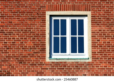 Reddish brick wall with a  window in a sunny day.