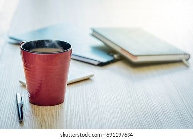 The reddish brown coffee cup is on the wood table and pen, the diary book is blurred background.