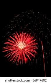 Reddish orange burst of fireworks with white interior near rocket trail and falling embers