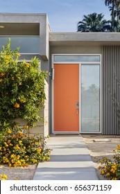 Reddish orange front door of a mid-century house