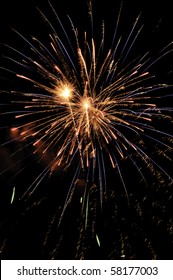 Reddish-orange pyrotechnic display laced with blue streaks and falling embers
