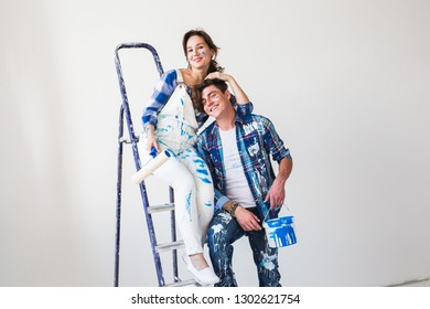 Redecoration, family and renovation concept - Funny young woman and man standing on the ladder