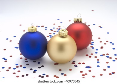 Red,gold, and blue Christmas ornaments with confetti.