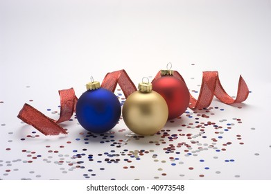 Red,gold, and blue Christmas ornaments with red ribbon.