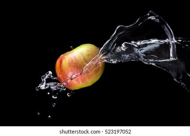 red-green apple in water splashes on black background