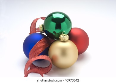Red,green,gold, and blue Christmas ornaments with red ribbon.