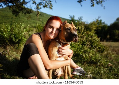 redhair jouful young woman caressing their dog, wearing sport clothing, enjoying their time and vacation in sunny park