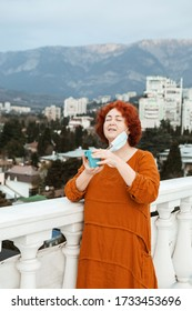 Redhair woman outdoors on a rooftop of her home without medical mask. Drinking tea and relaxing in self-isolation.  No mask. Coronavirus  pandemic concept.