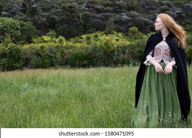 Red-haired 18th century woman in an embroidered bodice and black cloak standing in long grass