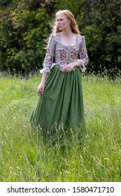 Red-haired 18th century woman wearing an embroidered bodice and wandering in long grass
