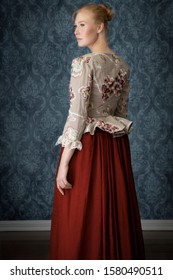 red-haired 18th century woman wearing an embroidered bodice