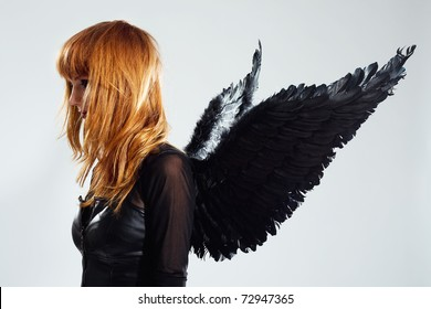 Red-haired angel girl with black wings