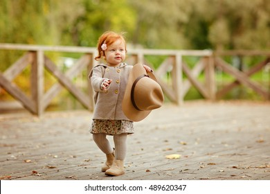 Red-haired baby girl in a hat smiling outdoors in autumn