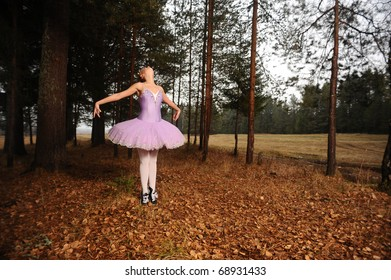 red-haired ballet dancer in sneakers dance among forest