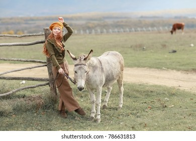 Red-haired beautiful girl in nature with a donkey