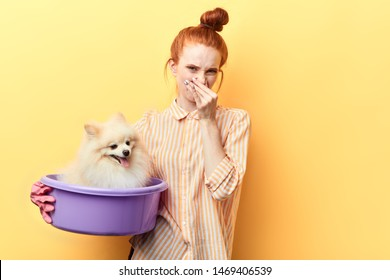 red-haired beautiful woman holds fingers to her nose because her dog is dirty and it needs to be washed. close up portrait, woman takes care of her pet.unpleant smell from pet