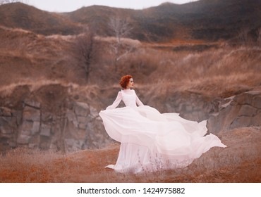 Red-haired beauty in a white vintage dress, stands on top of a hill, Background of the rocky mountains. Luxurious outfit with a long train flutters in the wind. Light flying silk fabrics. warm colors