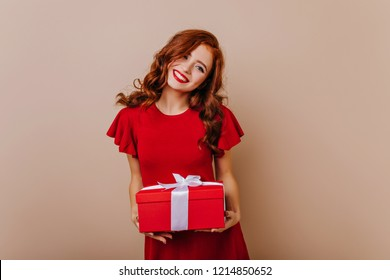 Red-haired birthday girl smiling to camera. Winsome female model in red dress holding christmas present.
